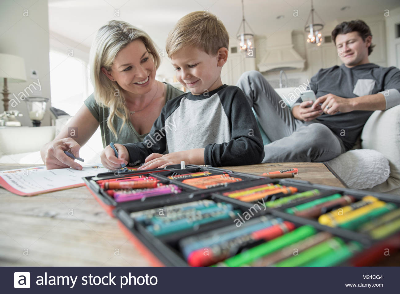 Mother and son coloring in living room - Stock Image