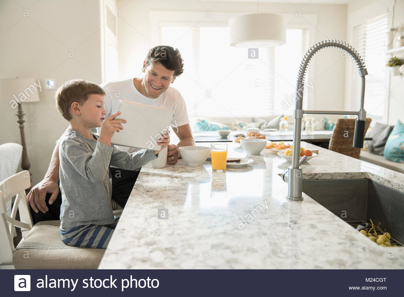 Father and son eating breakfast and using digital tablet at kitchen island - Stock Image