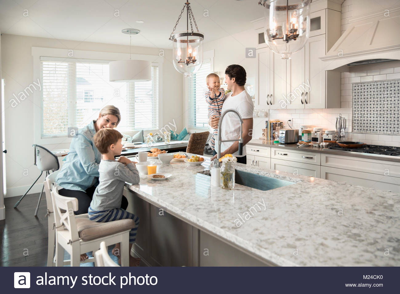 Family eating breakfast at kitchen island - Stock Image