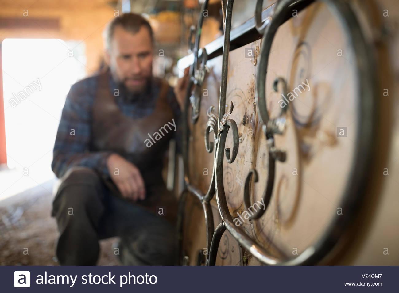 Male blacksmith examining scrolled metal - Stock Image