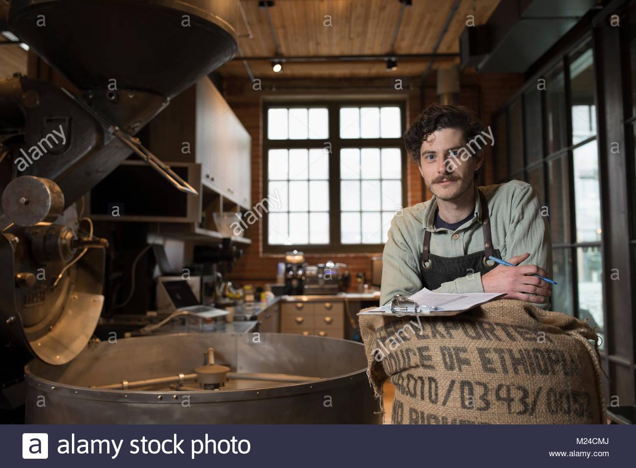Portrait confident male coffee roaster roasting coffee - Stock Image