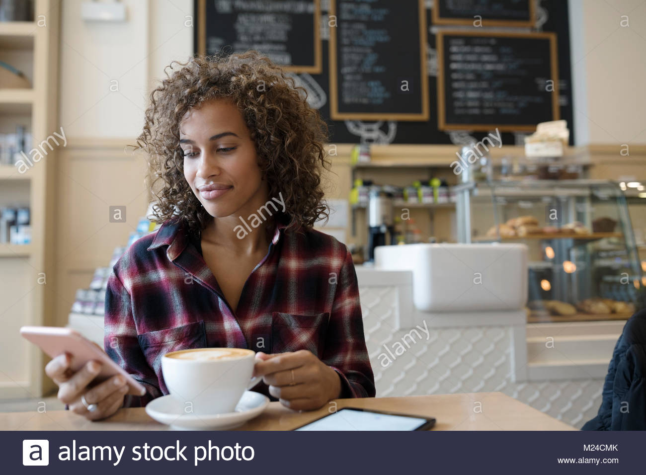 Young woman texting with smart phone and drinking cappuccino in cafe - Stock Image