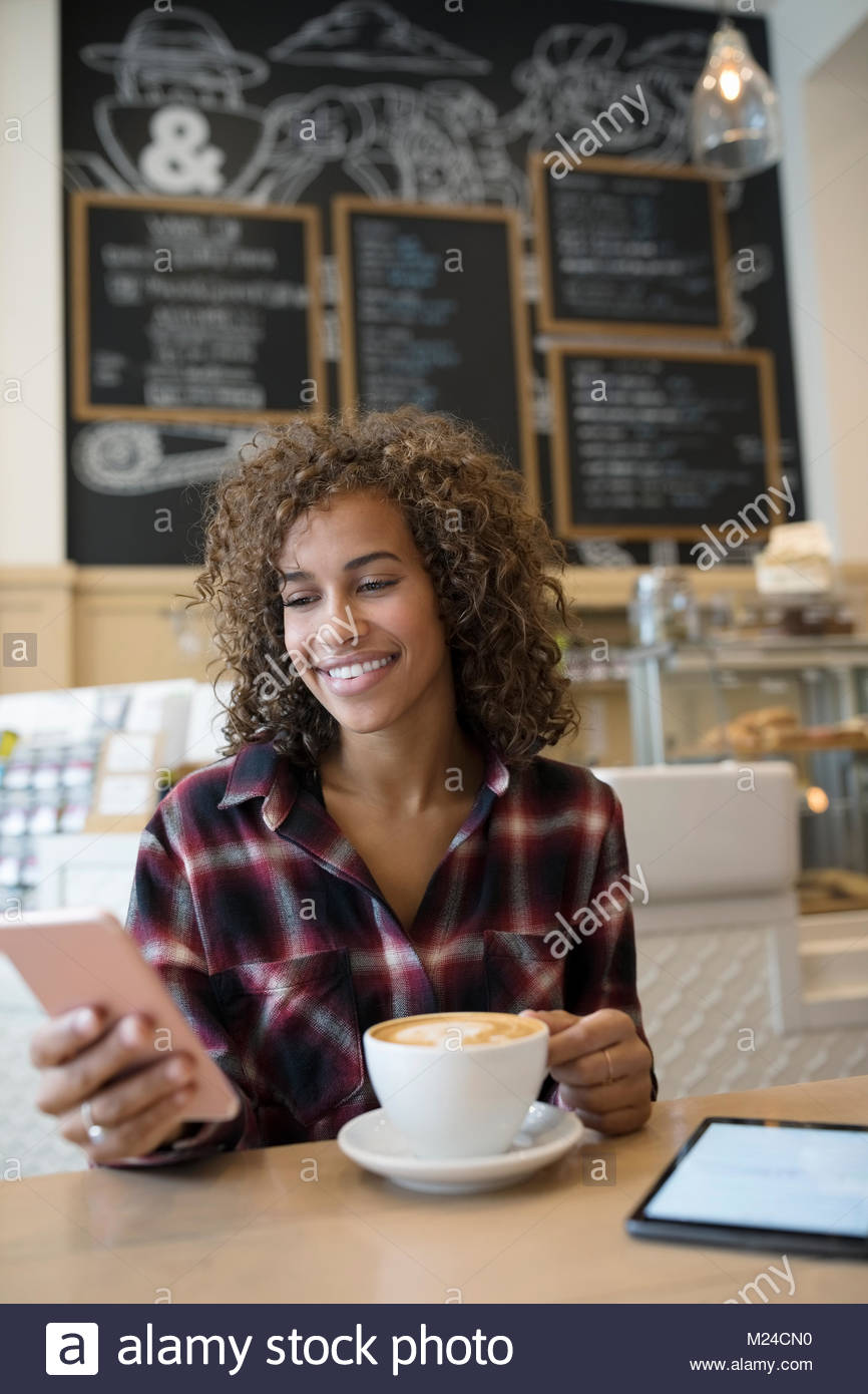 Smiling young woman texting with smart phone and drinking cappuccino in cafe - Stock Image