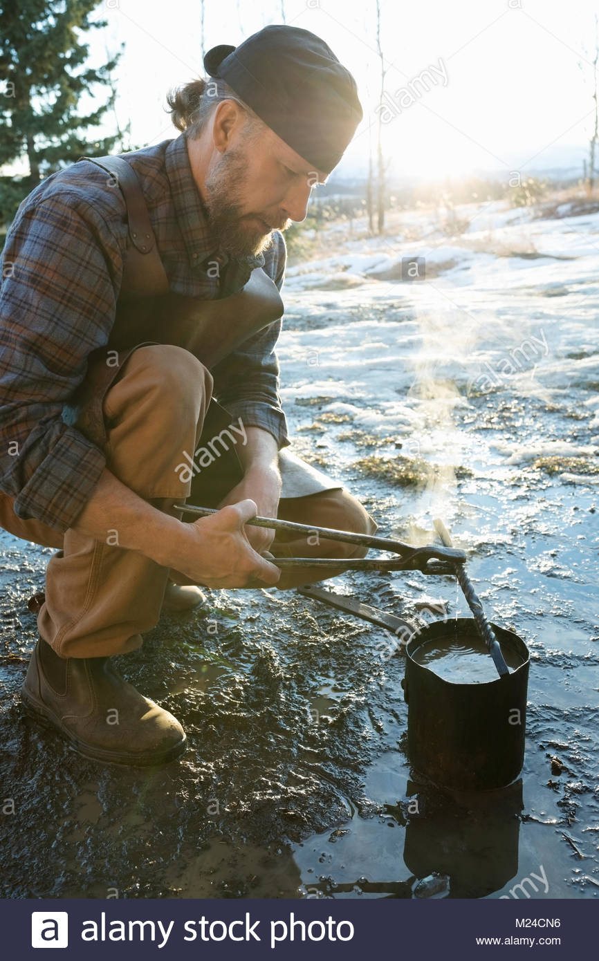 Male blacksmith cooling metal outdoors - Stock Image