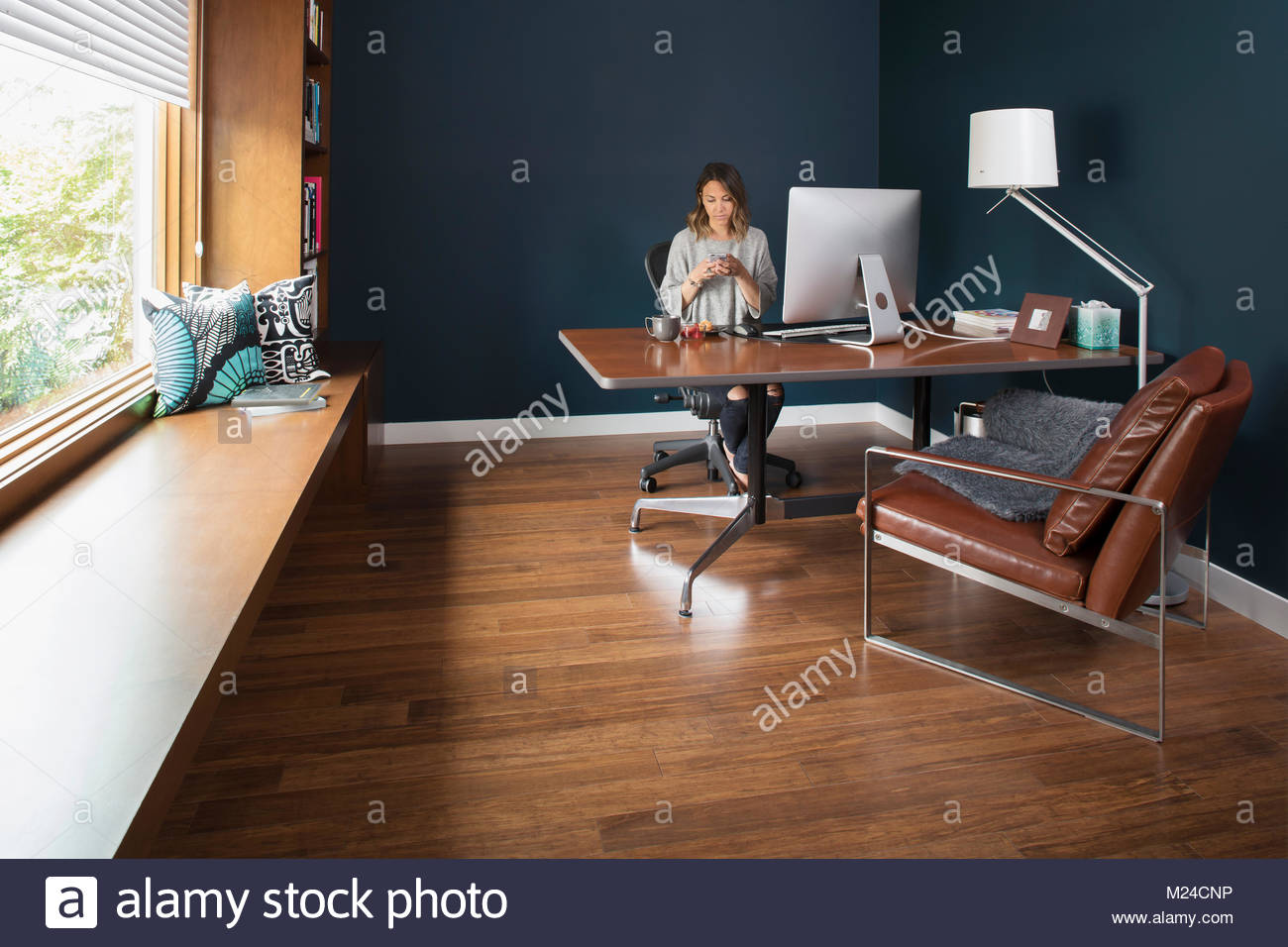 Woman texting with smart phone at computer in home office - Stock Image