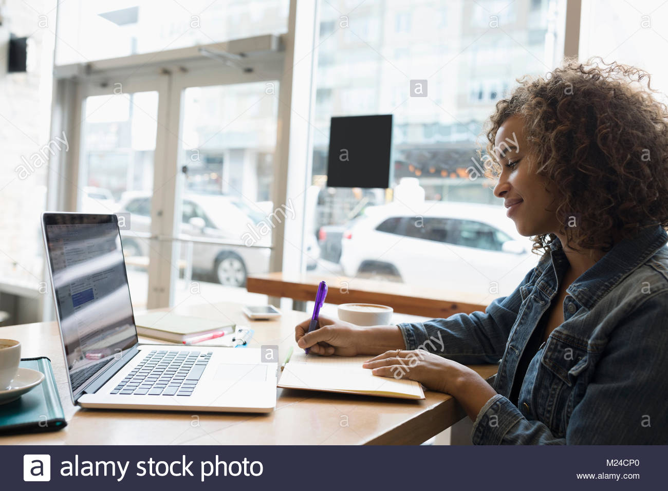 Smiling woman working at laptop, taking notes in cafe - Stock Image