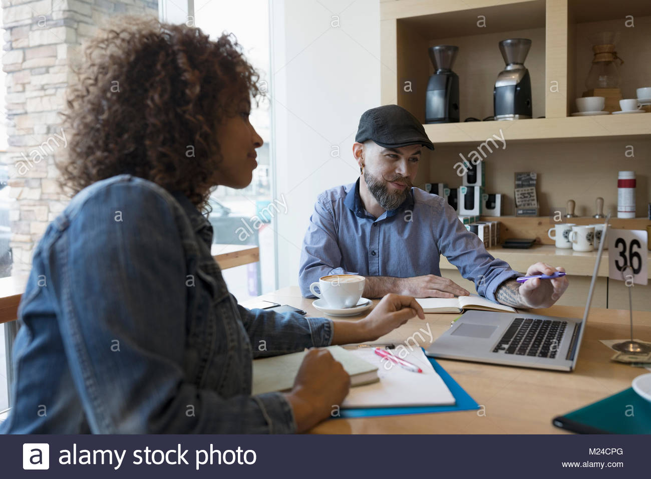 Small business owners working at laptop in cafe - Stock Image
