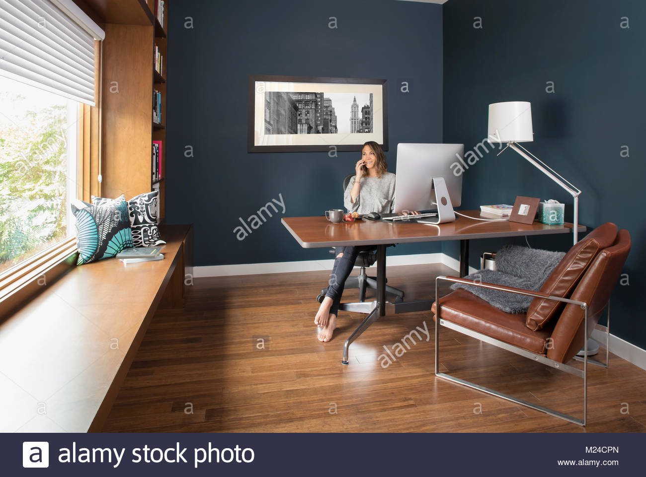 Woman talking on cell phone at computer in home office - Stock Image