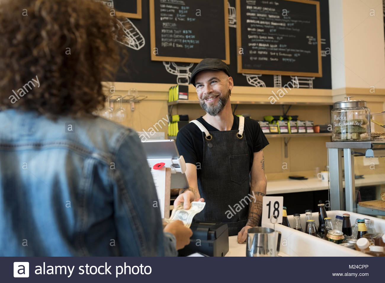 Friendly male barista taking money from female customer in cafe - Stock Image