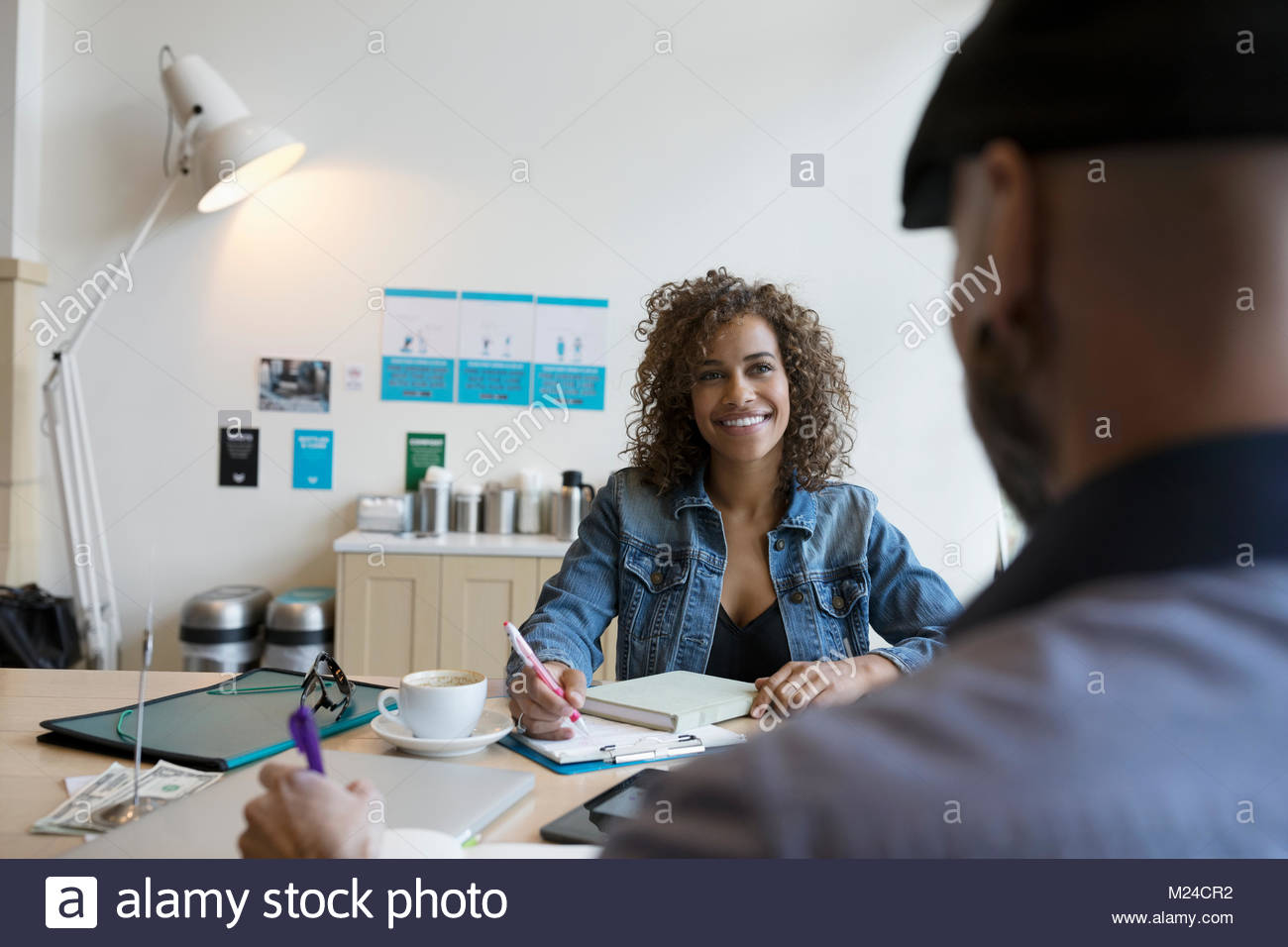 Smiling small business owners working, planning at table - Stock Image