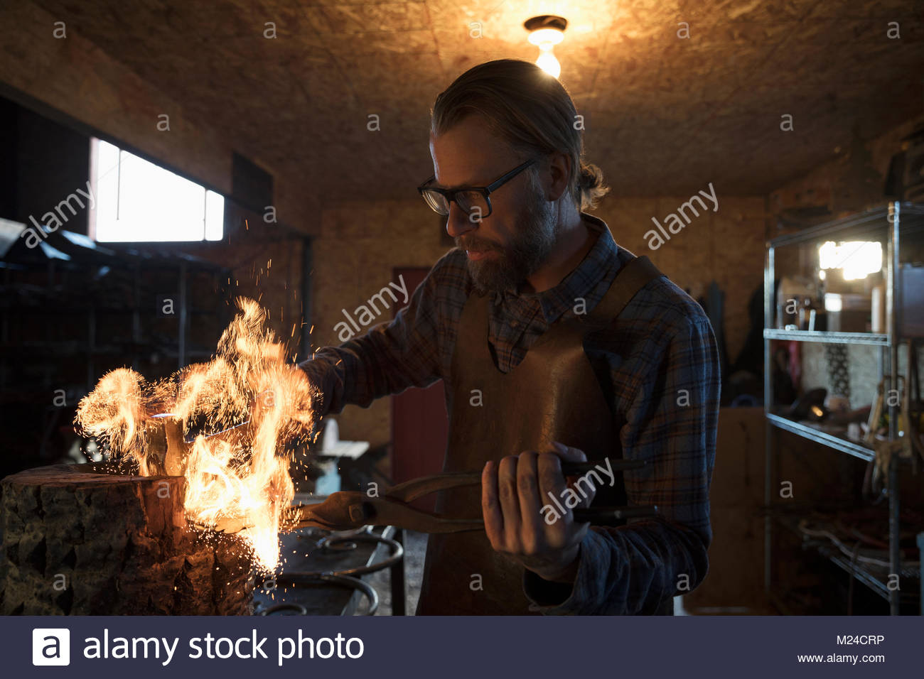 Focused male blacksmith heating metal at flame in blacksmith shop - Stock Image