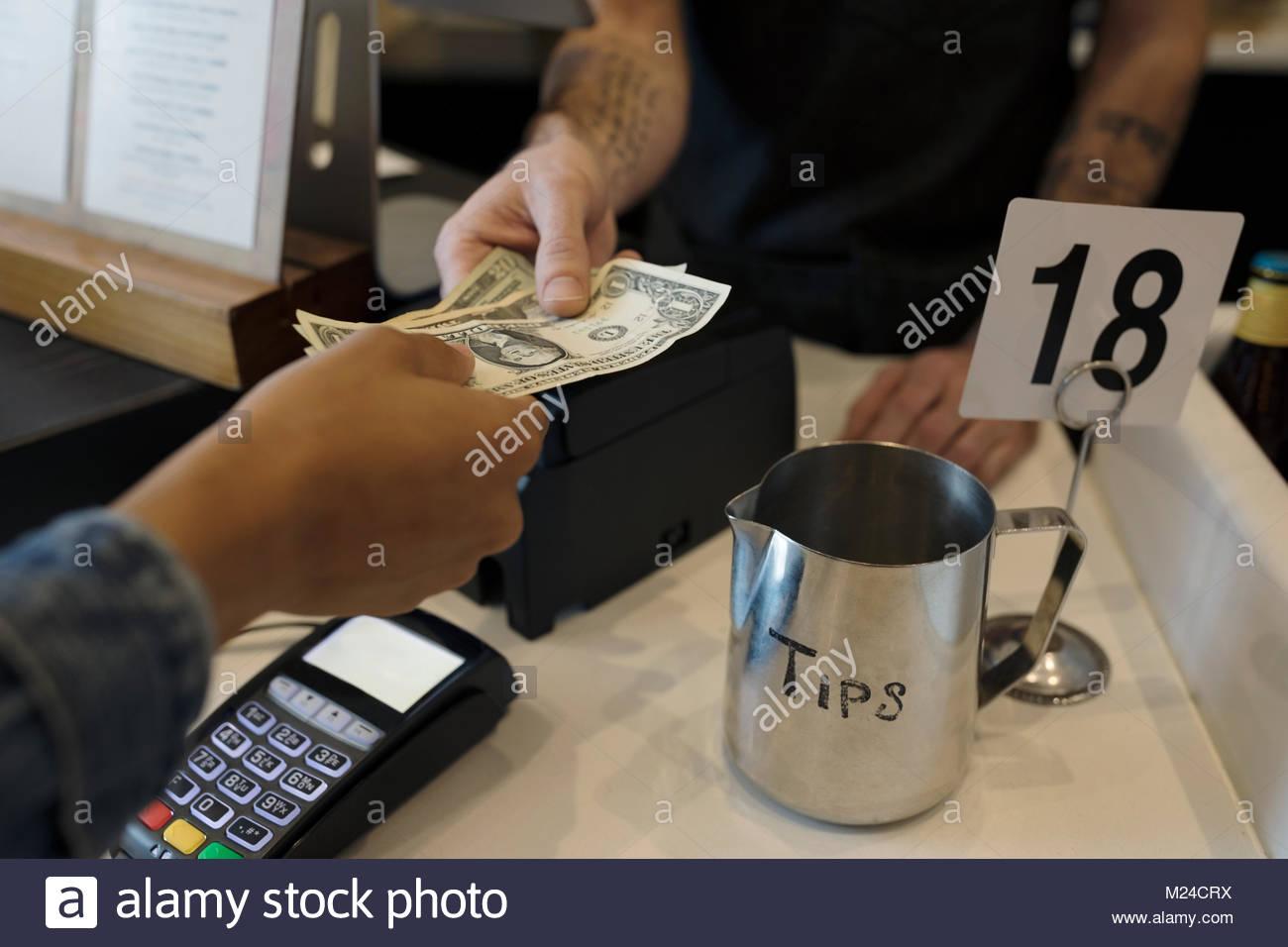 Close up customer paying cashier with cash next to tip jar - Stock Image