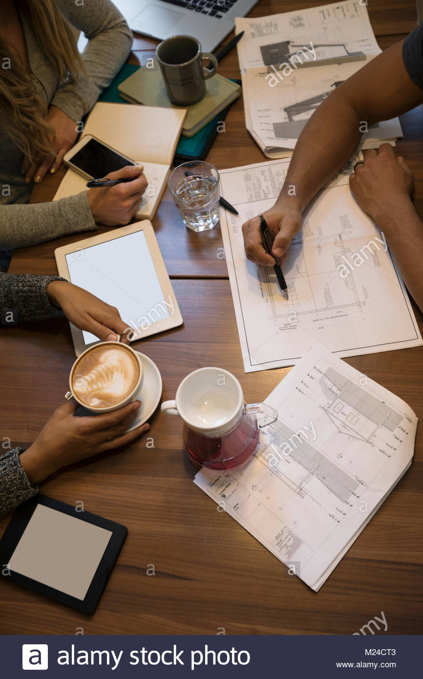 Overhead view business people drinking coffee, working, planning and discussing paperwork - Stock Image