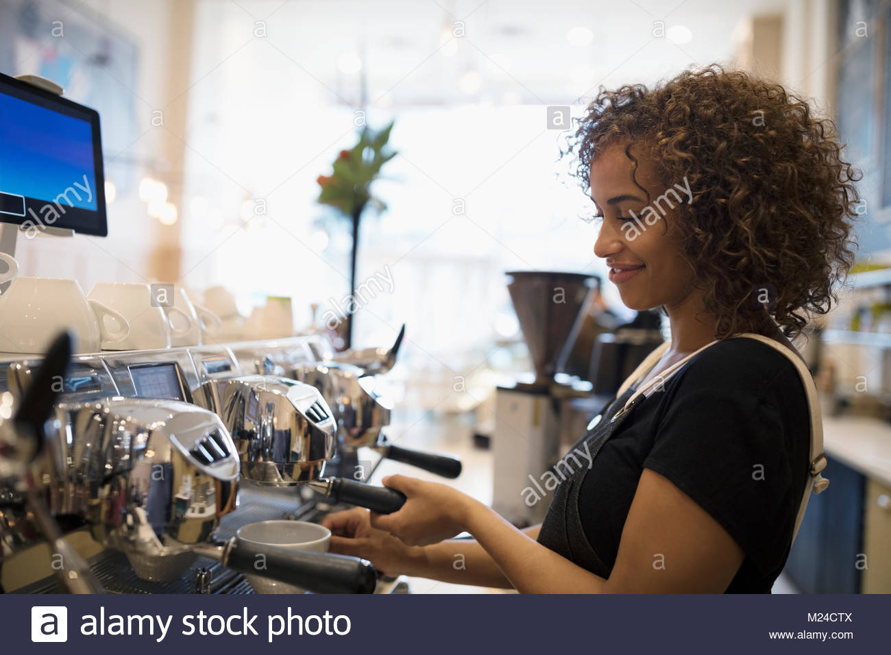 Smiling female barista making coffee at espresso machine in cafe - Stock Image