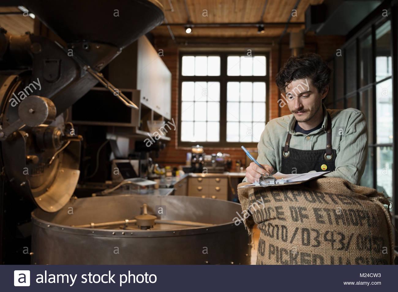 Male coffee roaster with clipboard roasting coffee - Stock Image