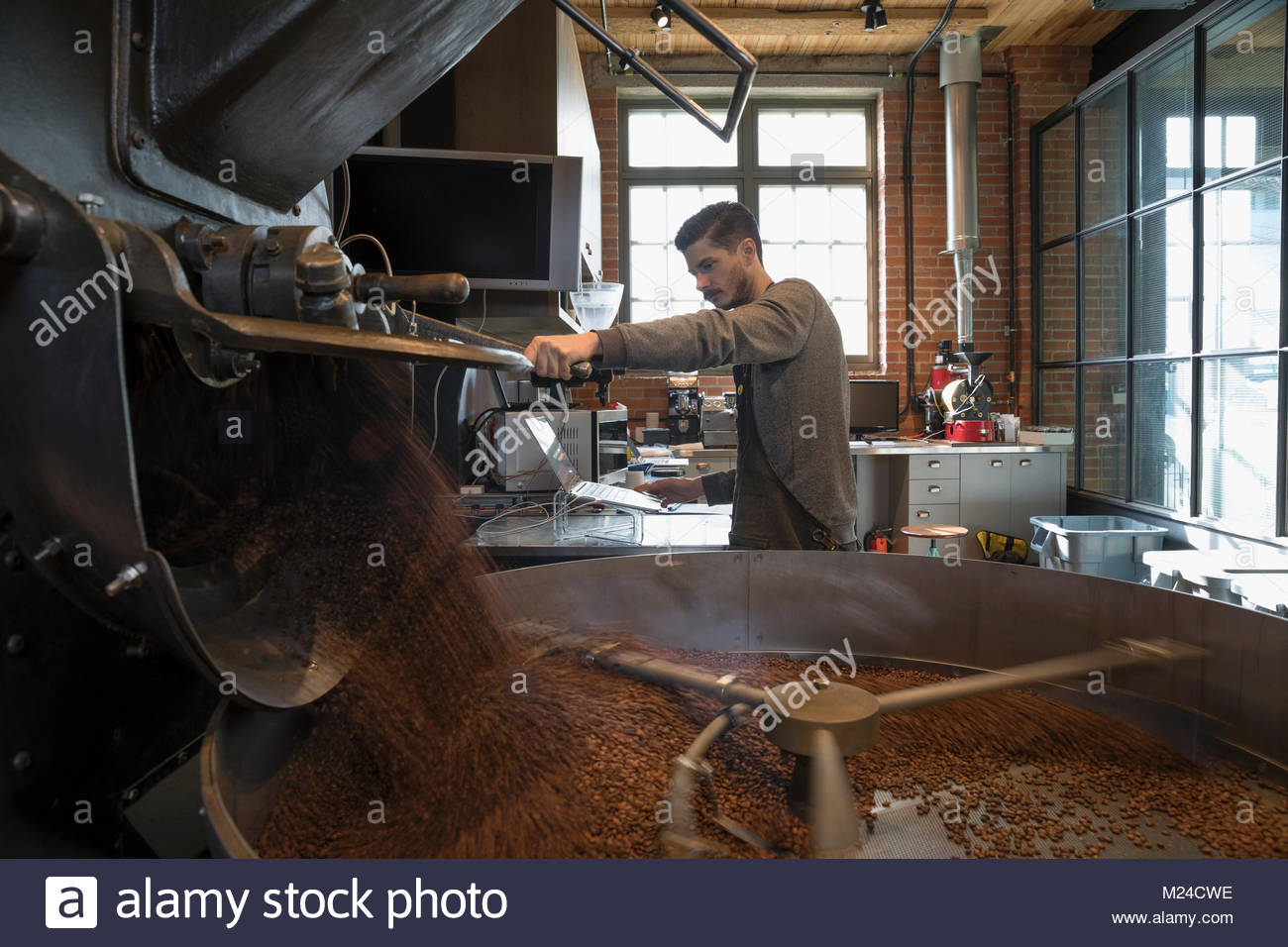 Male coffee roaster roasting coffee beans with large coffee roasting machine - Stock Image