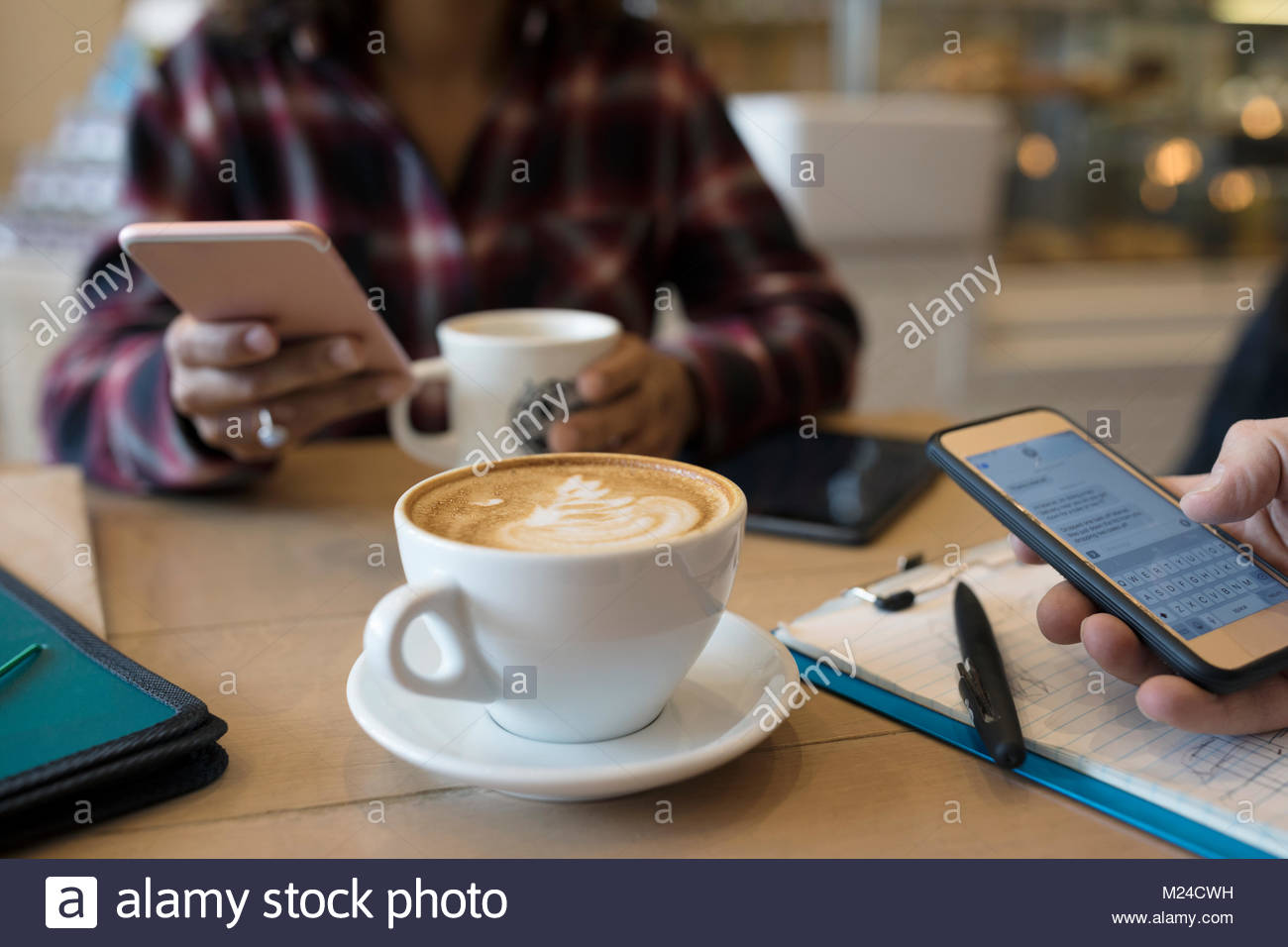 Woman texting with smart phone and drinking cappuccino coffee in cafe - Stock Image