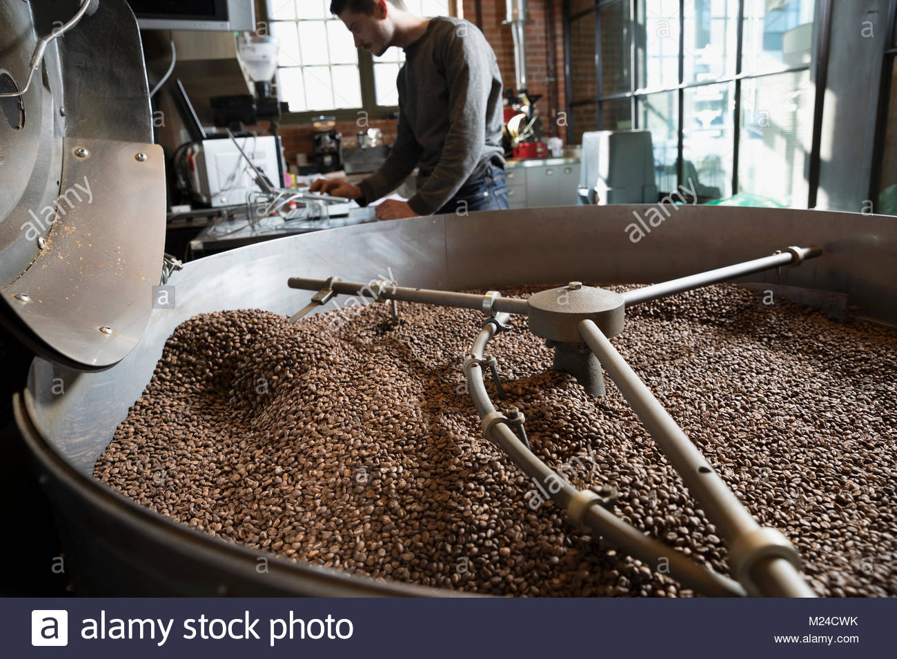 Coffee beans roasting in large coffee roaster - Stock Image