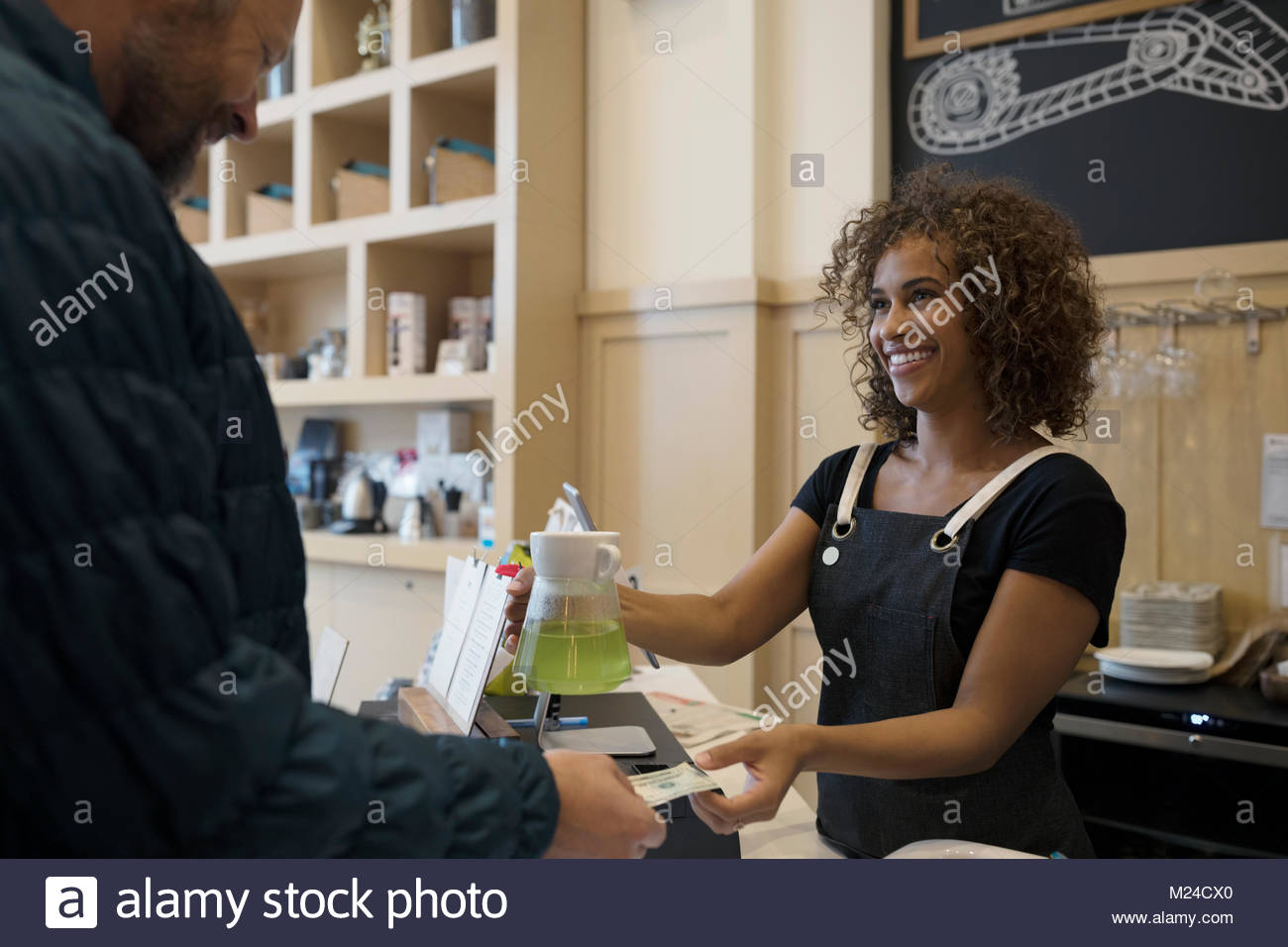 Smiling female barista taking money from male customer in cafe - Stock Image