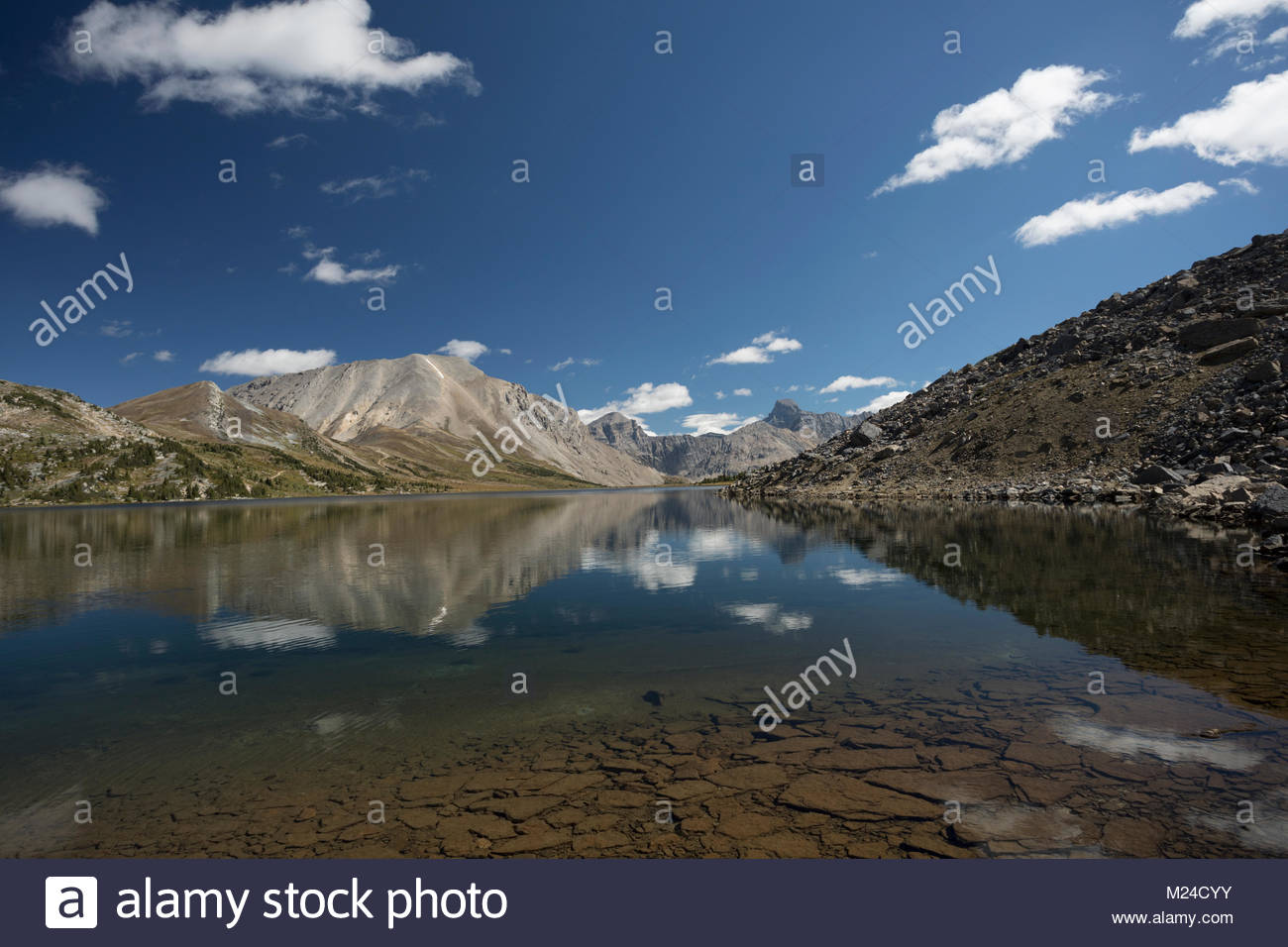 Reflection of clouds and craggy mountains on tranquil, placid lake - Stock Image