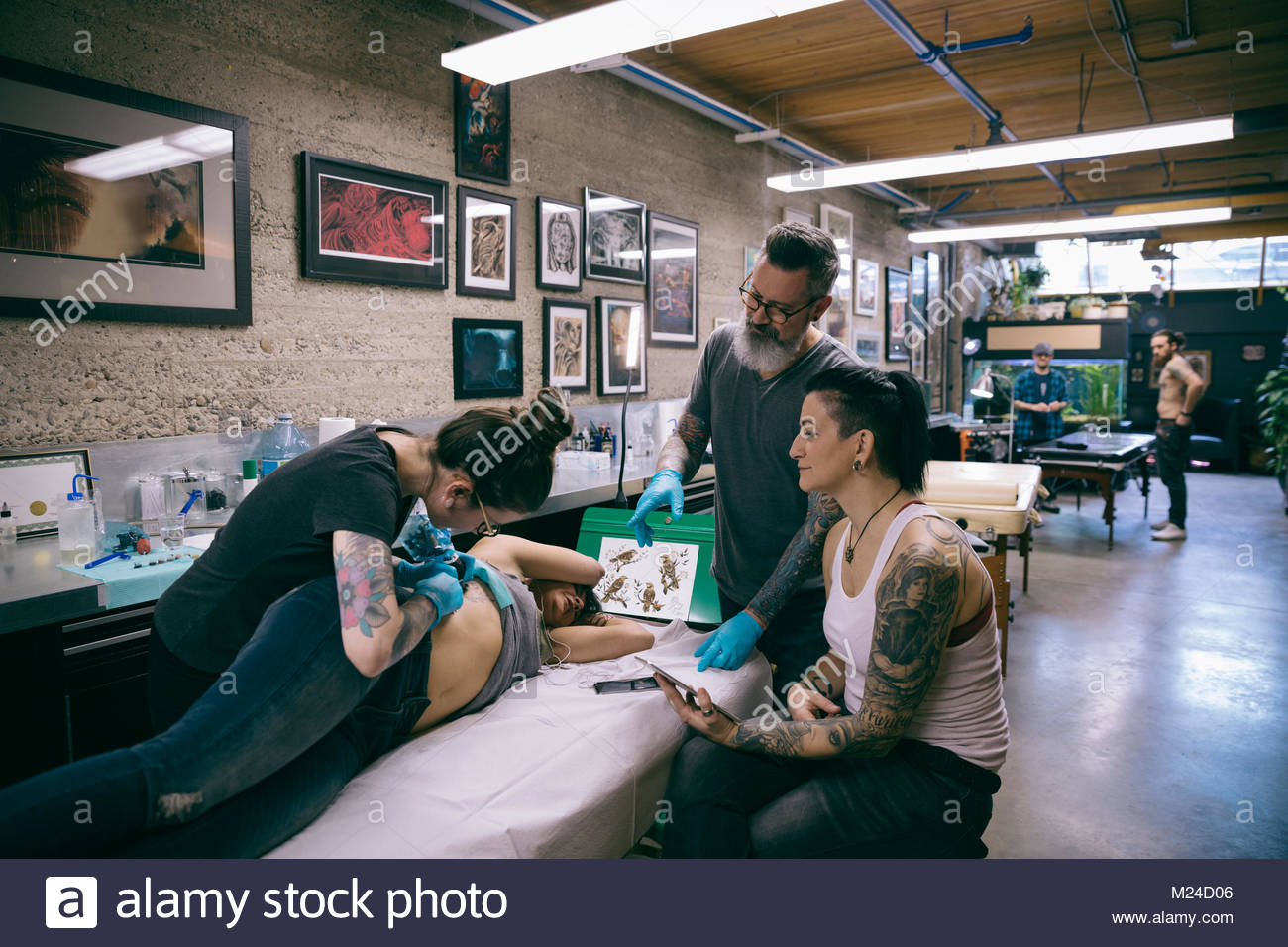 Tattoo artists and client tattooing side of client in tattoo studio - Stock Image