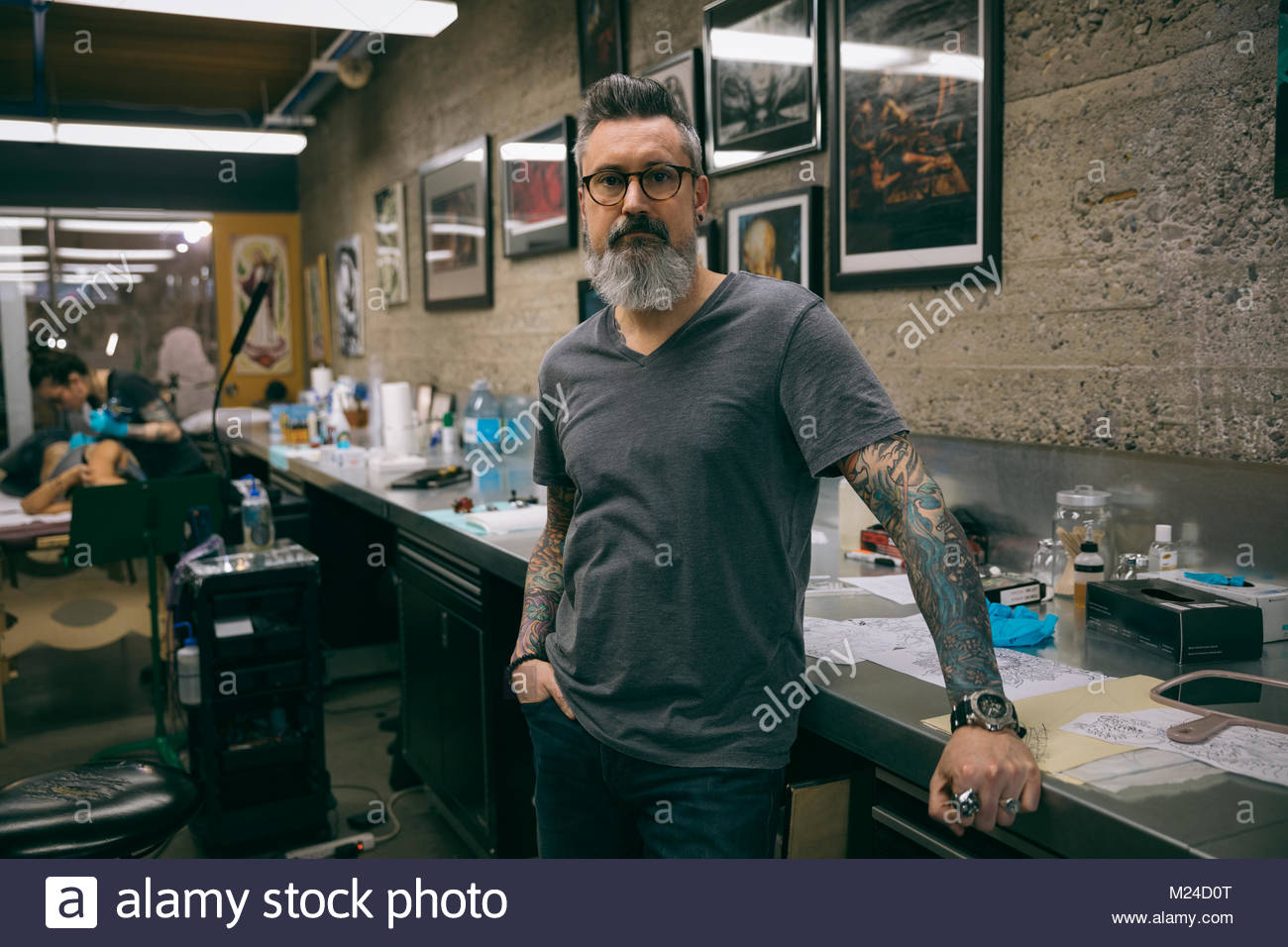 Portrait confident tattoo artist in tattoo studio - Stock Image