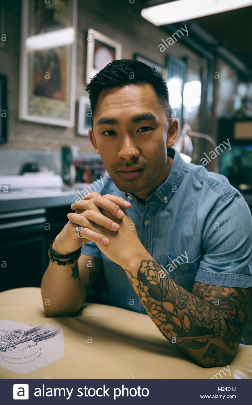 Portrait confident tattoo artist - Stock Image