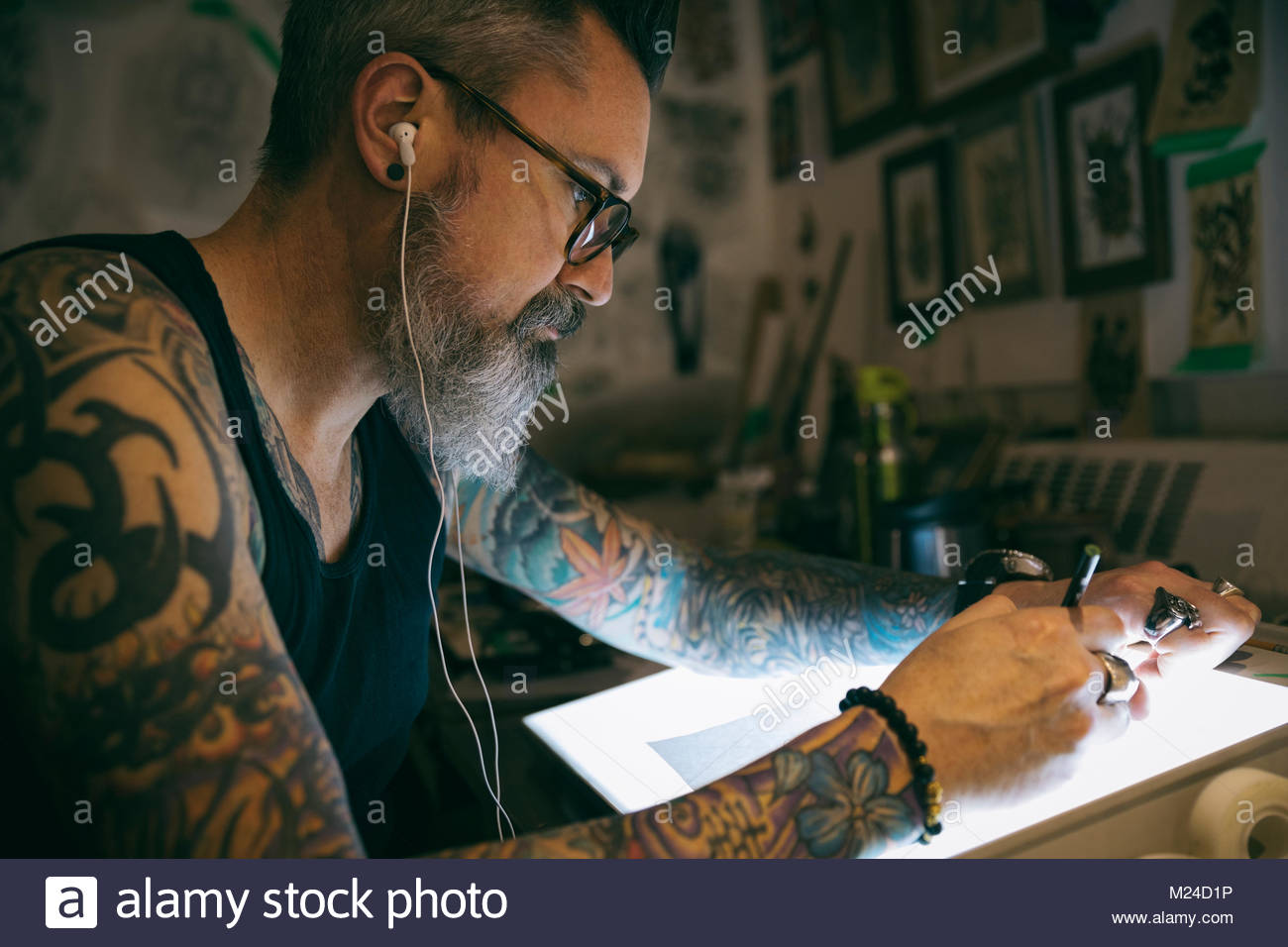 Tattoo artist listening to music and sketching at light table in dark tattoo studio - Stock Image