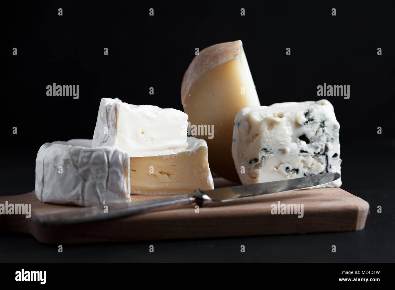Assortment of  cheese on a wooden plate with a vintage knife. Black background. Macro image. - Stock Image