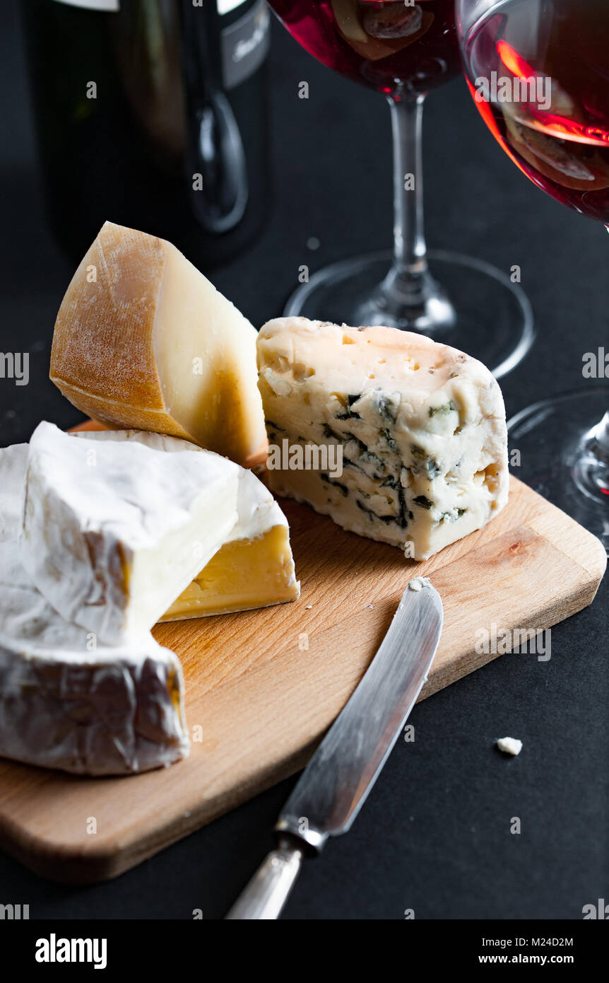 Assortment of cheeses  on a wooden plate with vintage silver knife and two glasses of red wine. Vertical. - Stock Image
