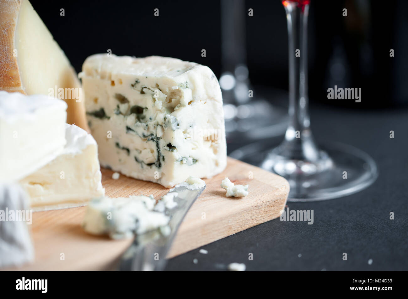 Cheese platter with piece of Roquefort cut by vintage knife and wine glasses on a backround. Black background. Macro - Stock Image