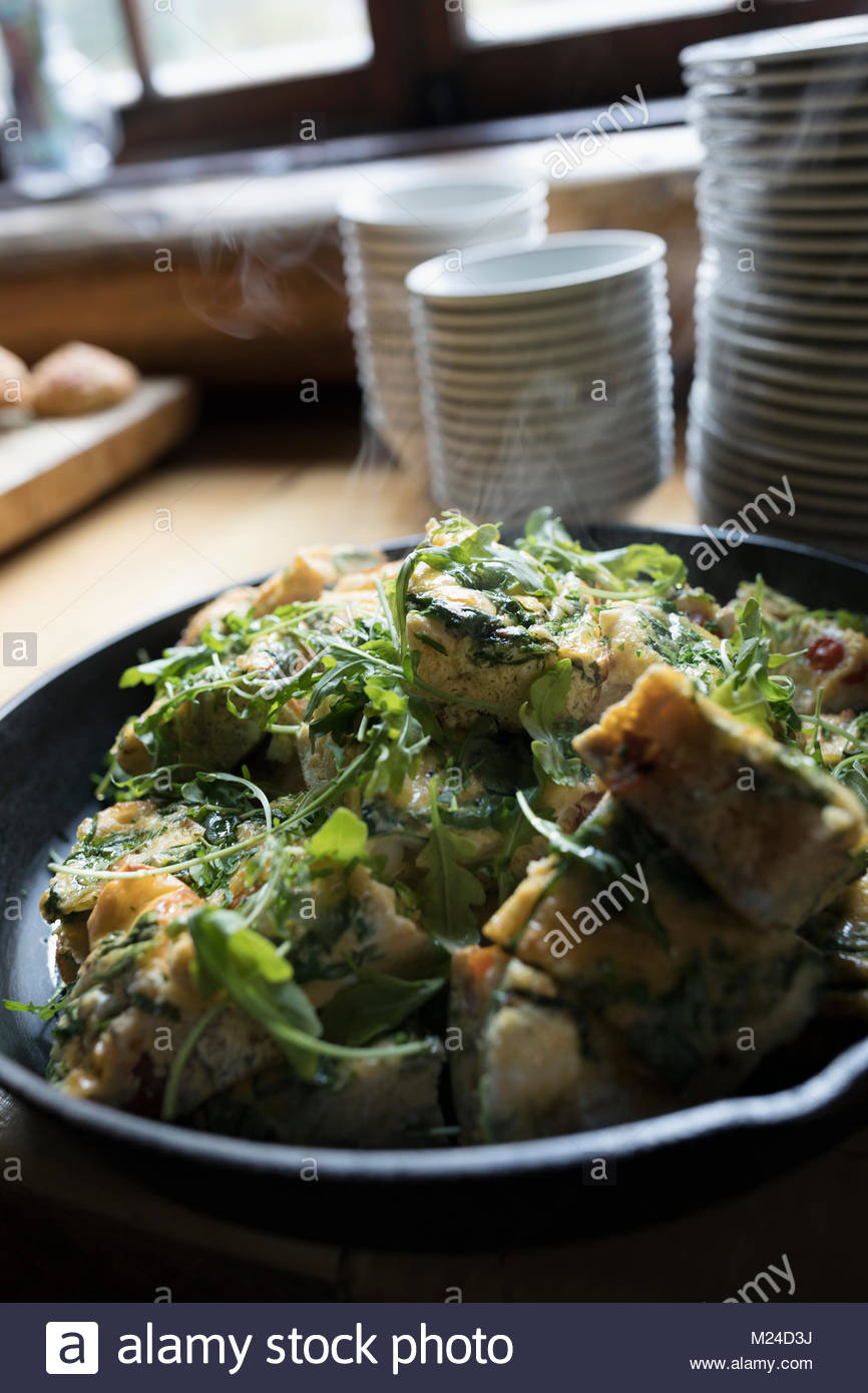 Still life steaming food in hot cast iron skillet - Stock Image
