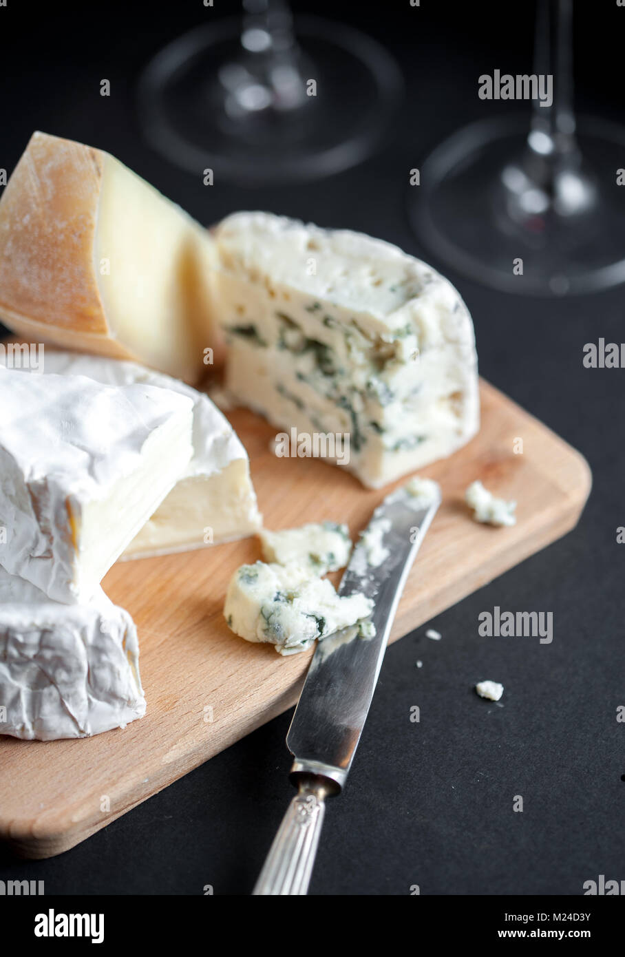 Assortment of cheeses  on a wooden plate with vintage silver knife and two wine glasses. Vertical. Macro image. - Stock Image
