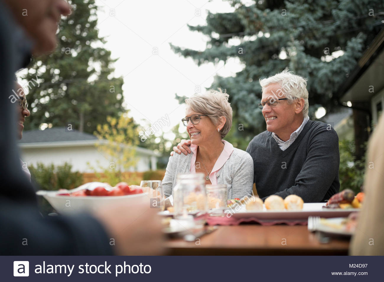 Smiling senior couple enjoying garden party lunch at patio table - Stock Image