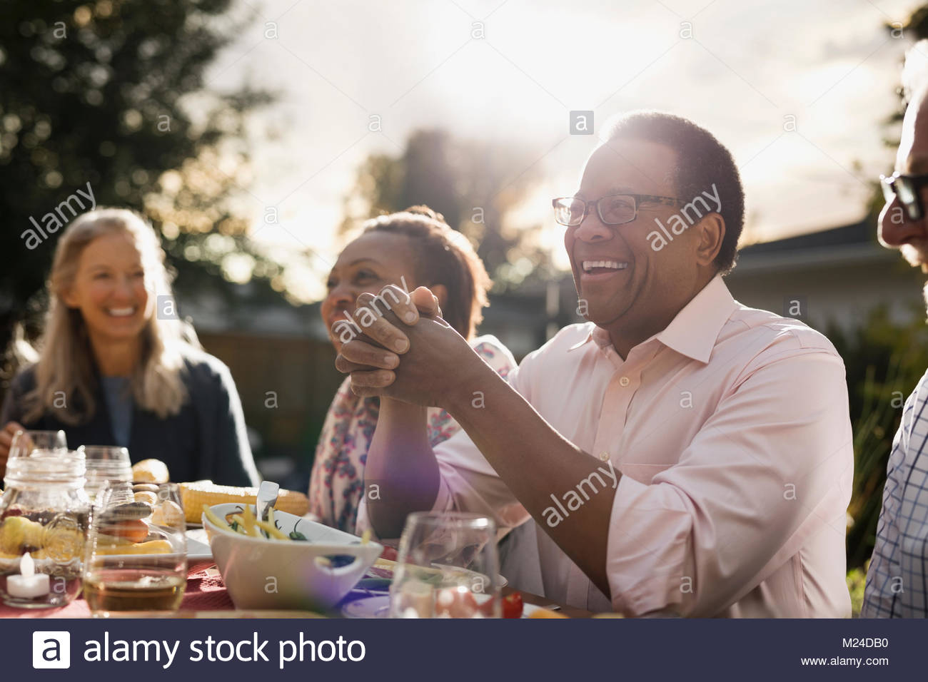 Laughing senior man enjoying garden party lunch with friends at sunny patio table - Stock Image