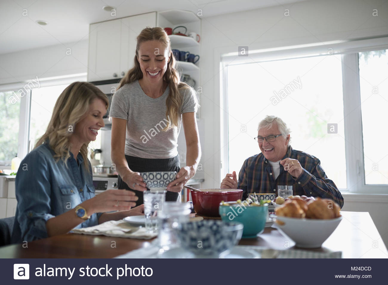 Smiling daughters and senior father eating at kitchen table - Stock Image