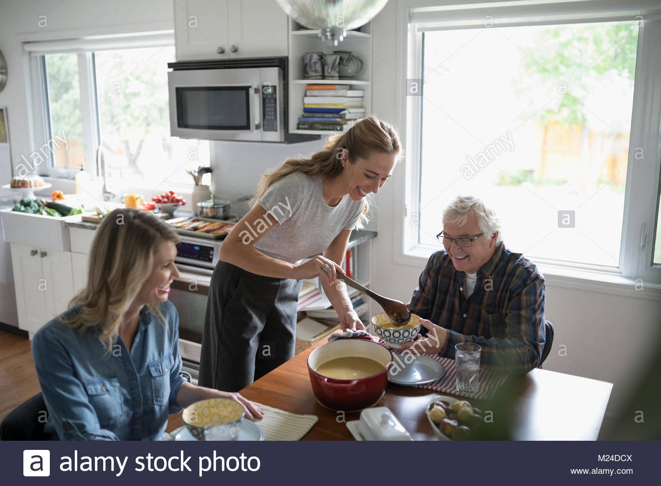 Daughters cooking, serving soup to senior father at kitchen table - Stock Image