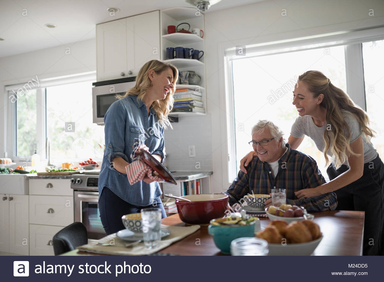 Smiling, affectionate daughters cooking for senior father at kitchen table - Stock Image