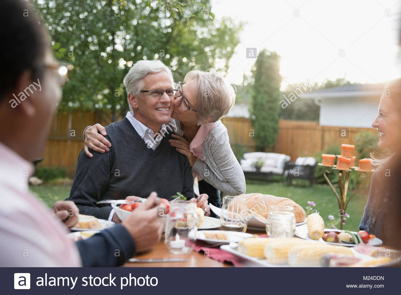 Affectionate senior wife kissing husband on cheek at garden party lunch patio table - Stock Image
