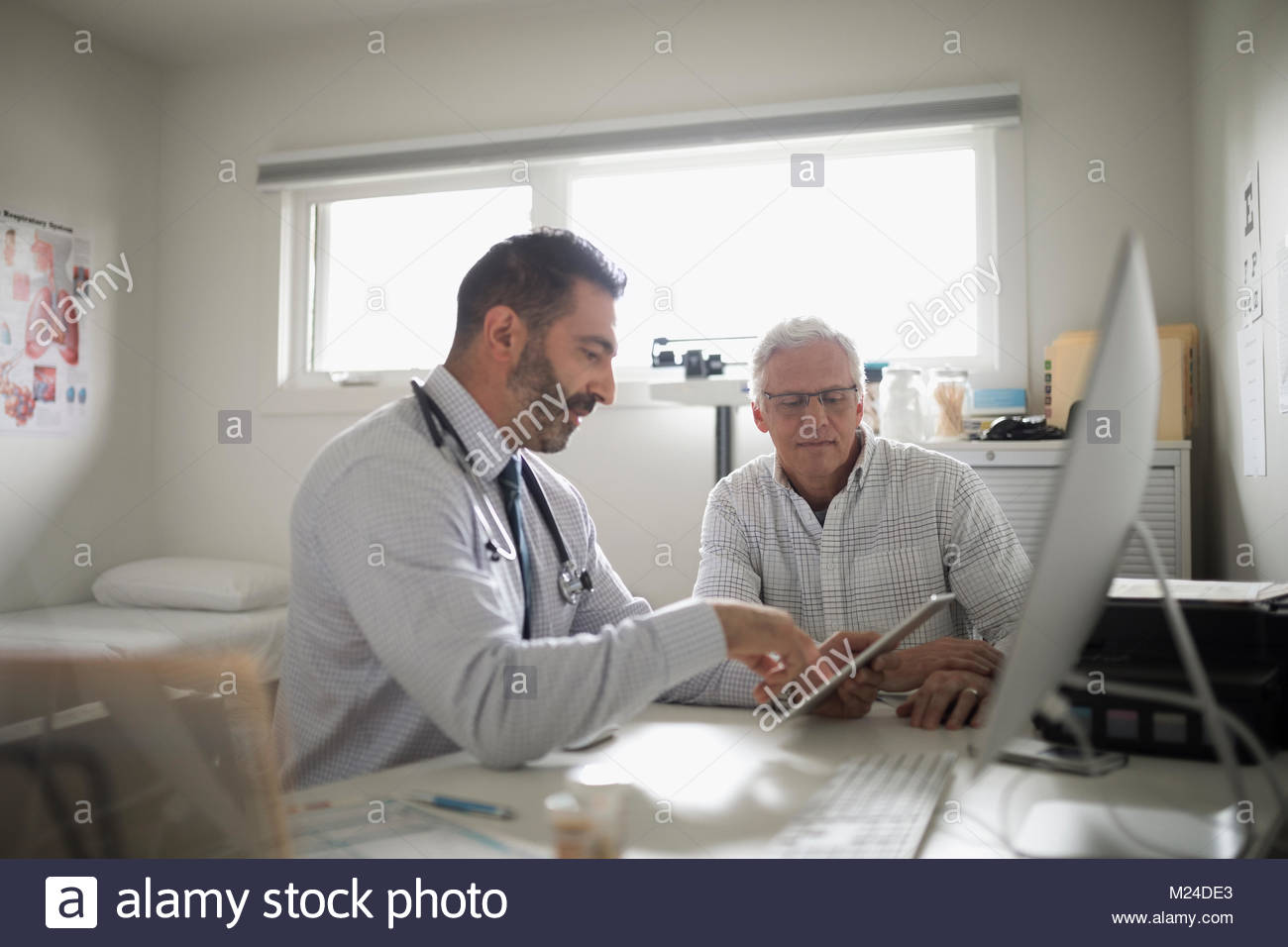 Male doctor with digital tablet talking with senior patient in doctor - Stock Image