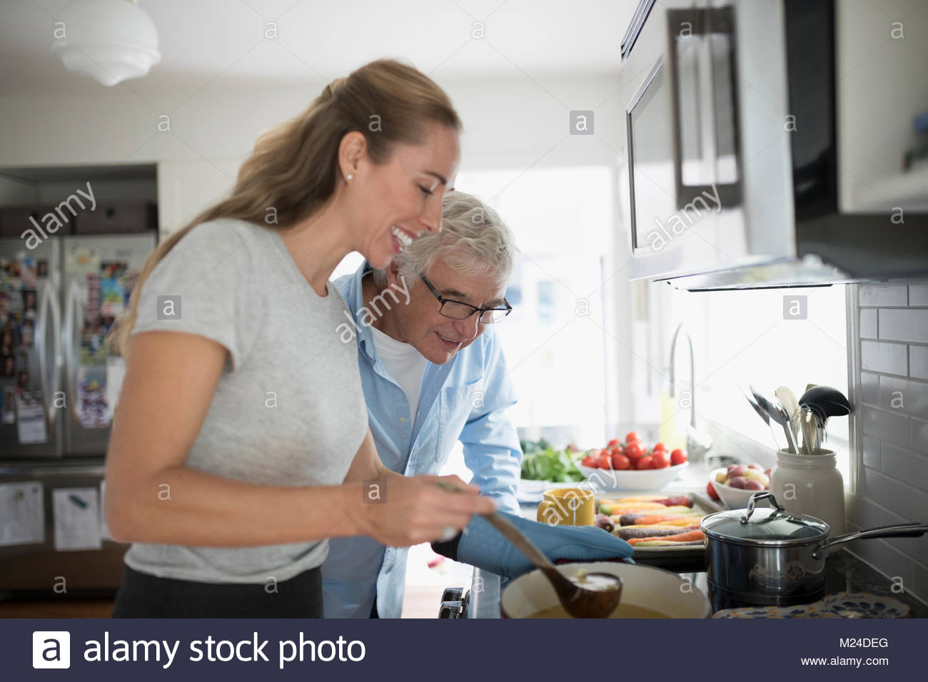 Smiling daughter and senior father cooking at stove in kitchen - Stock Image