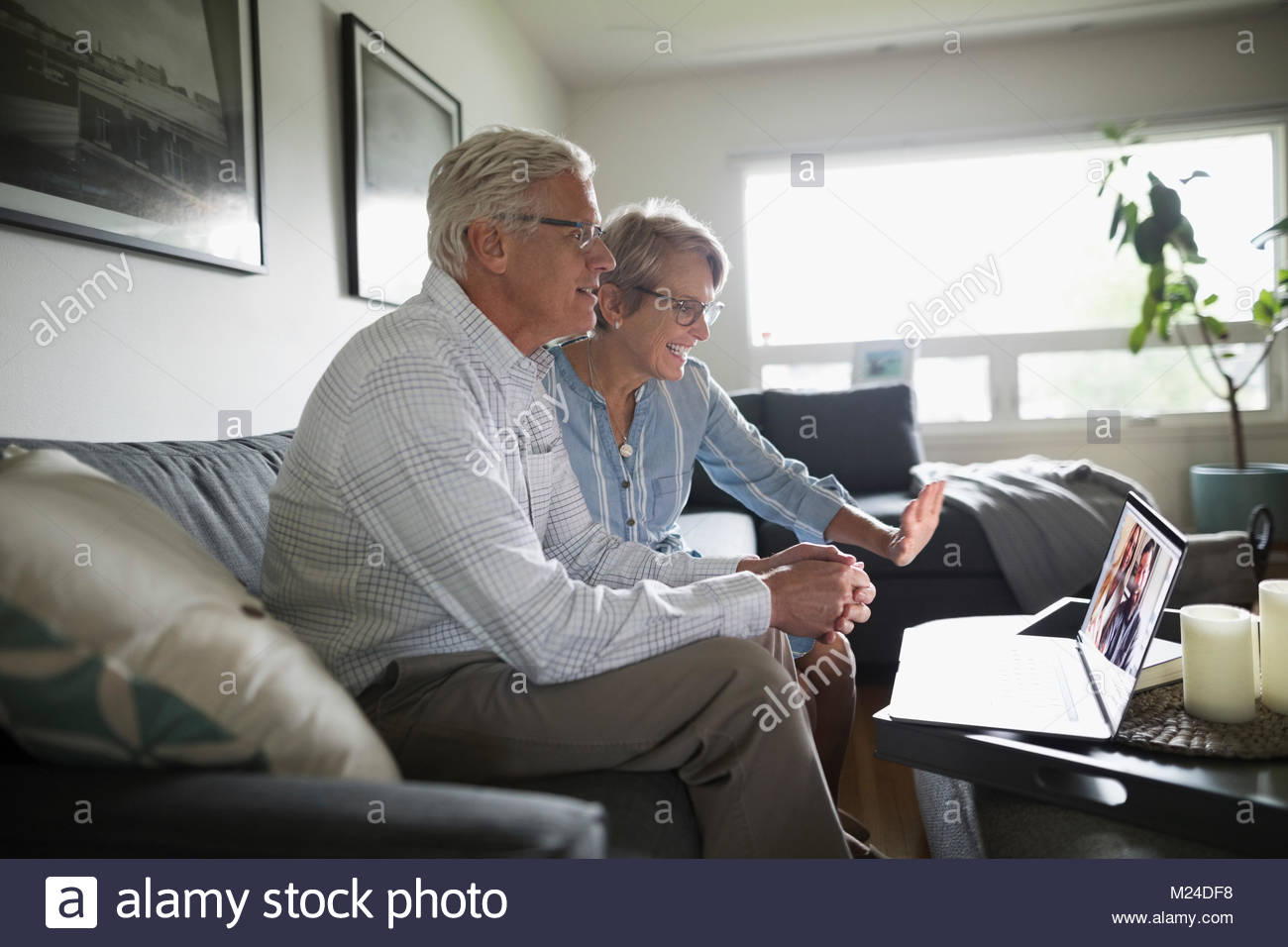 Senior couple waving, video chatting with laptop on living room sofa - Stock Image