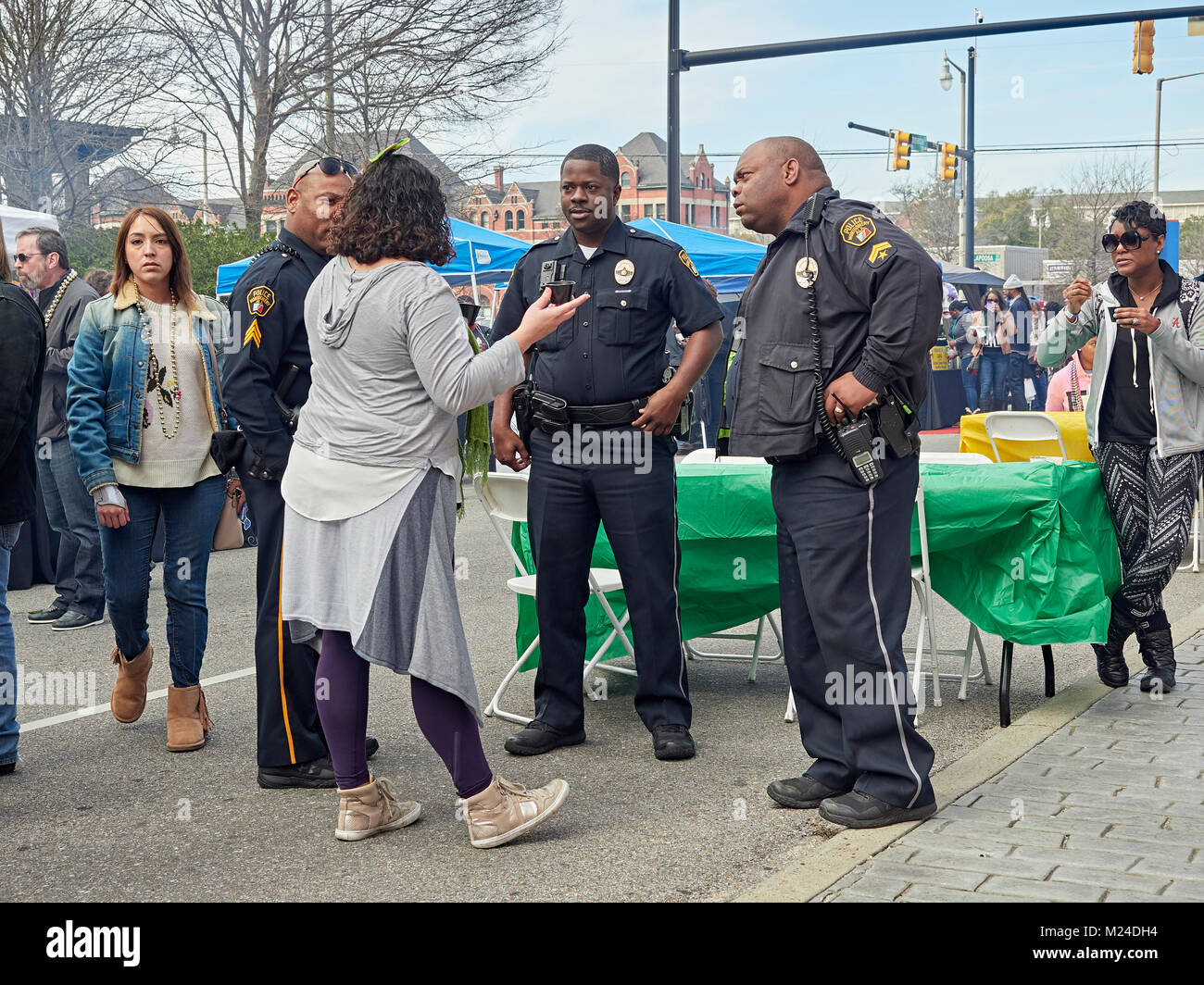 Three African American police officers politely talk with a mature adult woman at a street celebration in Montgomery - Stock Image