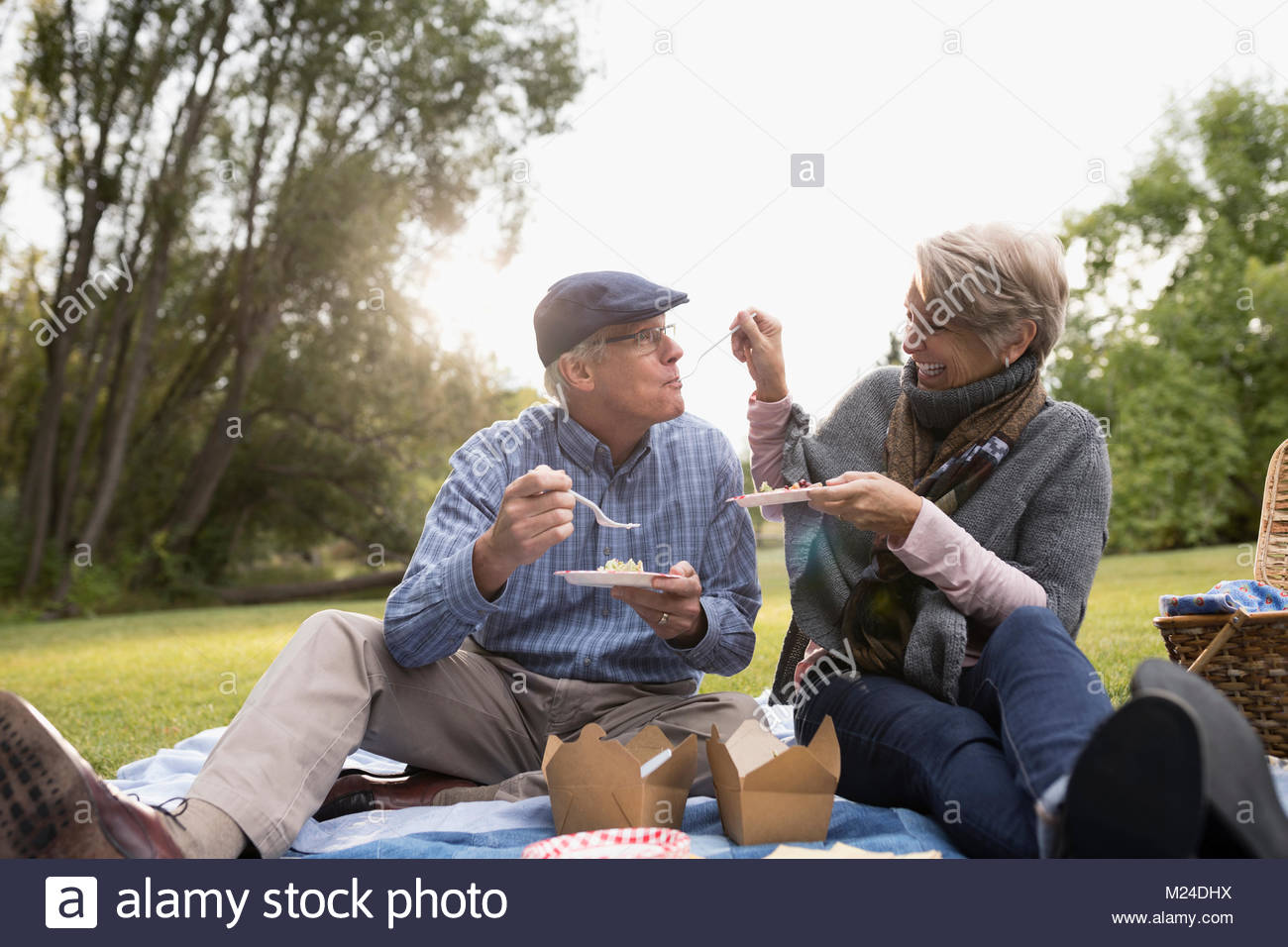 Senior couple eating, enjoying picnic in park - Stock Image