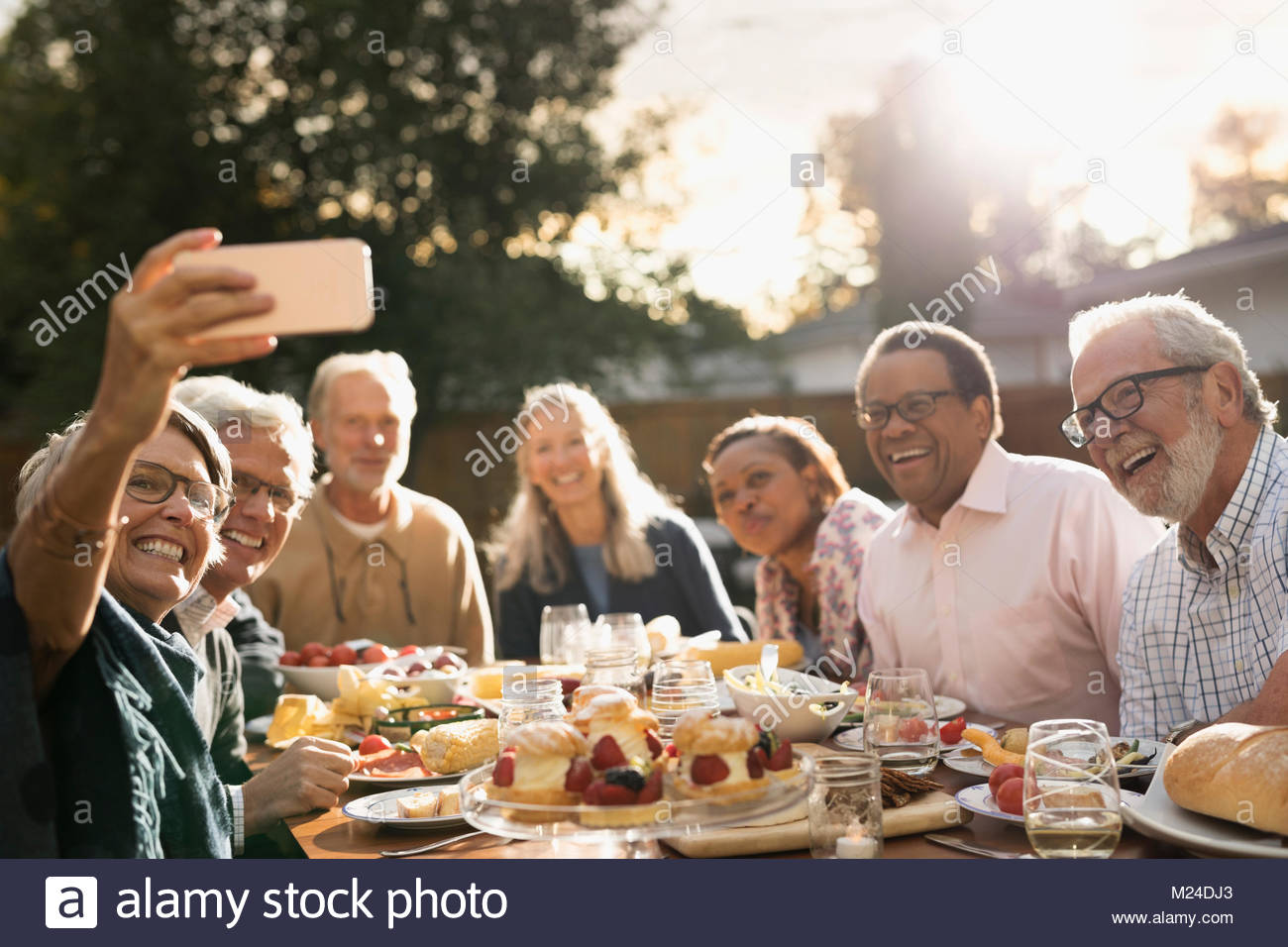 Smiling senior friends posing for selfie at garden party lunch at sunny patio table - Stock Image