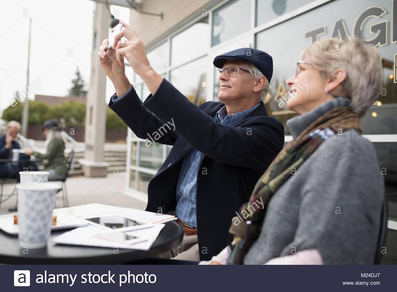 Senior couple using camera phone at sidewalk cafe - Stock Image