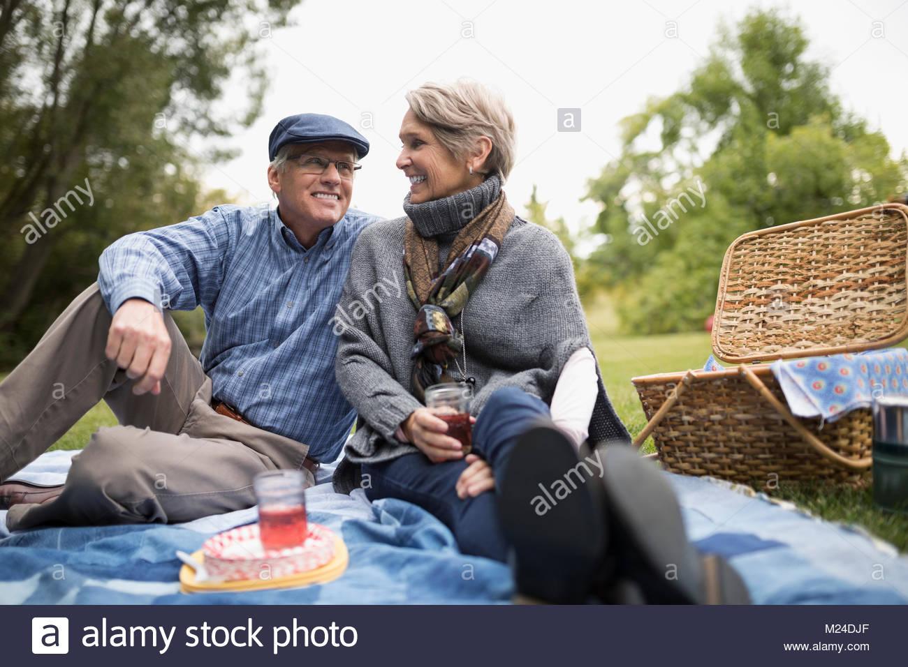 Senior couple enjoying picnic in park - Stock Image
