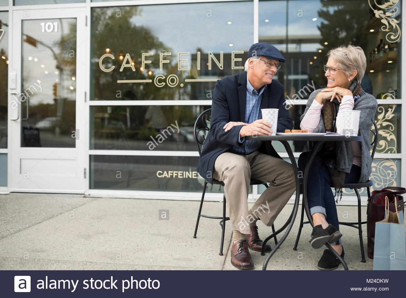 Senior couple drinking coffee and talking at sidewalk cafe - Stock Image