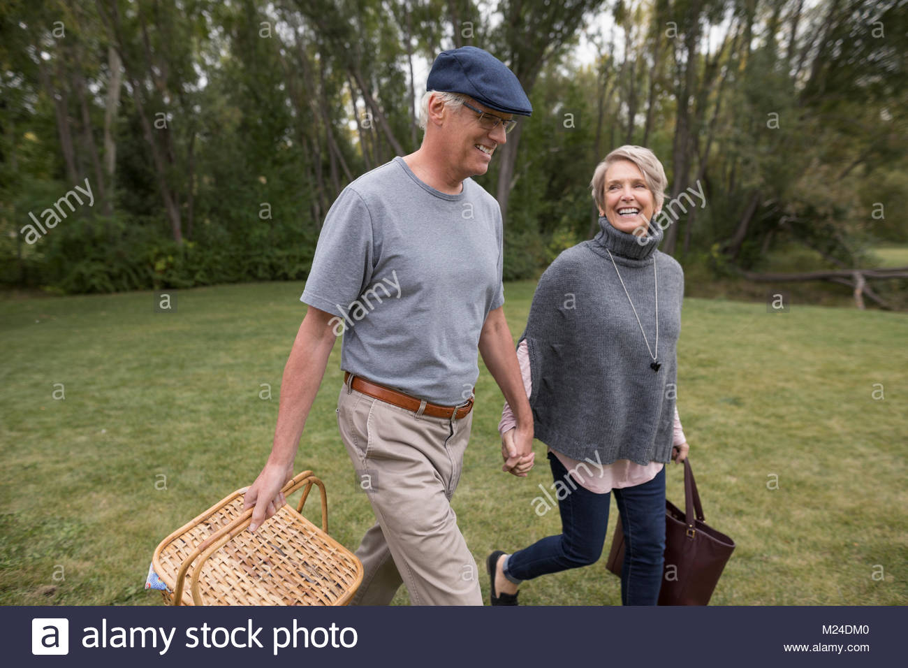 Smiling senior couple walking and holding hands, carrying picnic basket in park - Stock Image