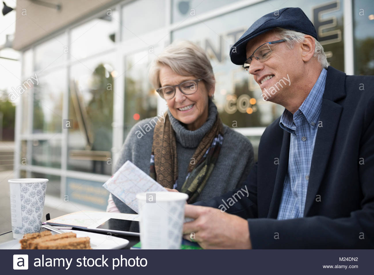 Senior couple looking at map, drinking coffee at sidewalk cafe - Stock Image